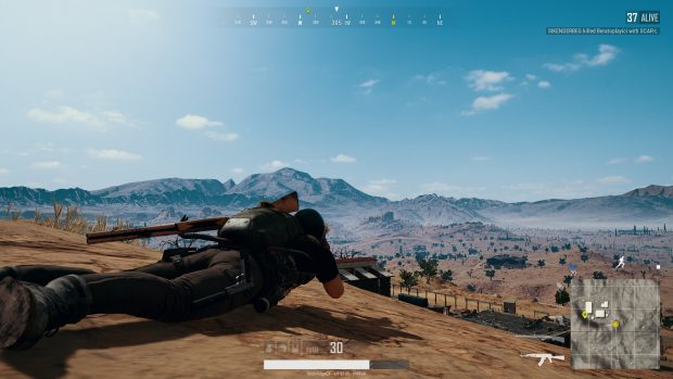 Player prone on top of a hill, searching for other players