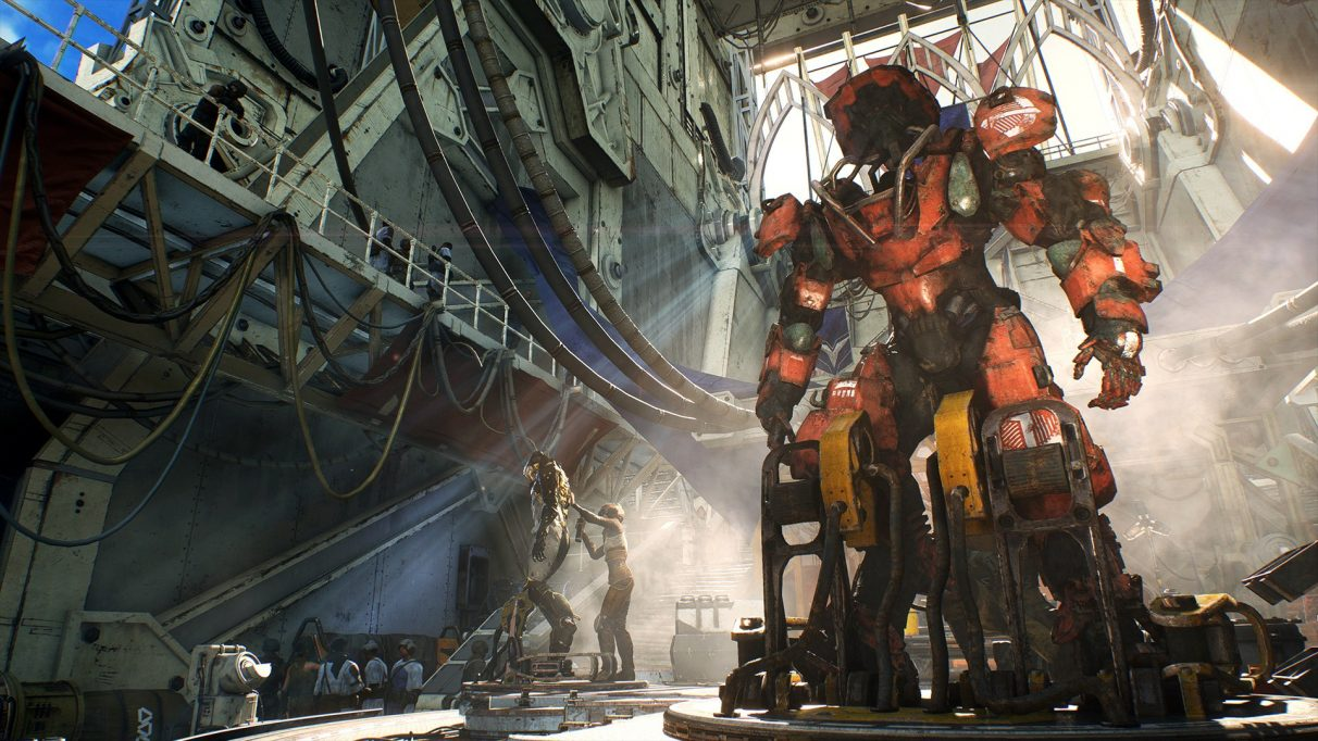 An engineer fixes some equipment while an empty giant mech suit looms over the top of her