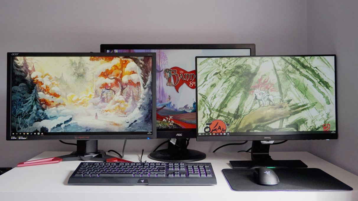 A photo of three gaming monitors on a table.