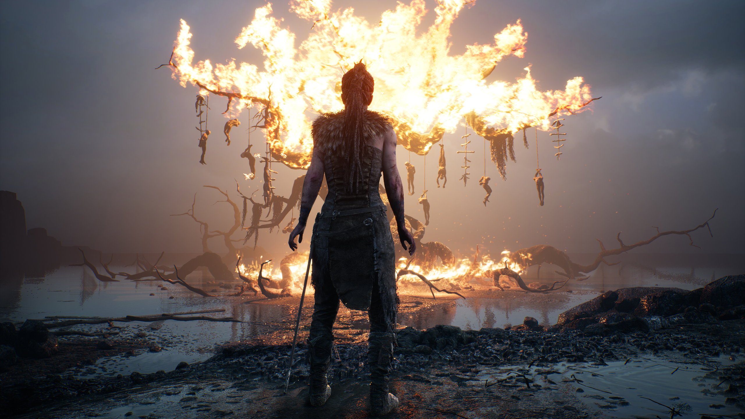 Senua stands before a burning tree with hanging corpses in a Hellblade screenshot.