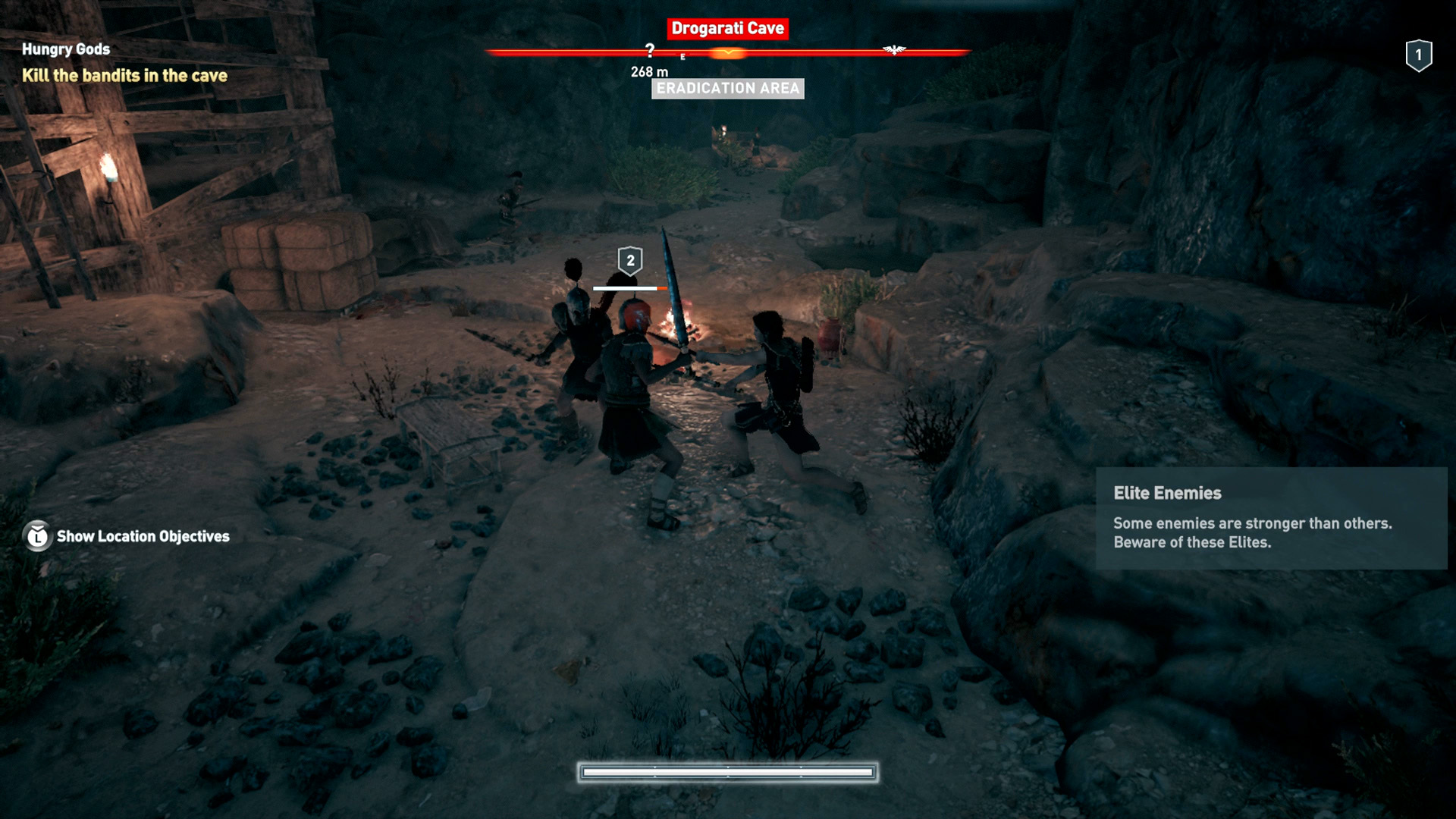 Kassandra fighting two bandits in a cave.