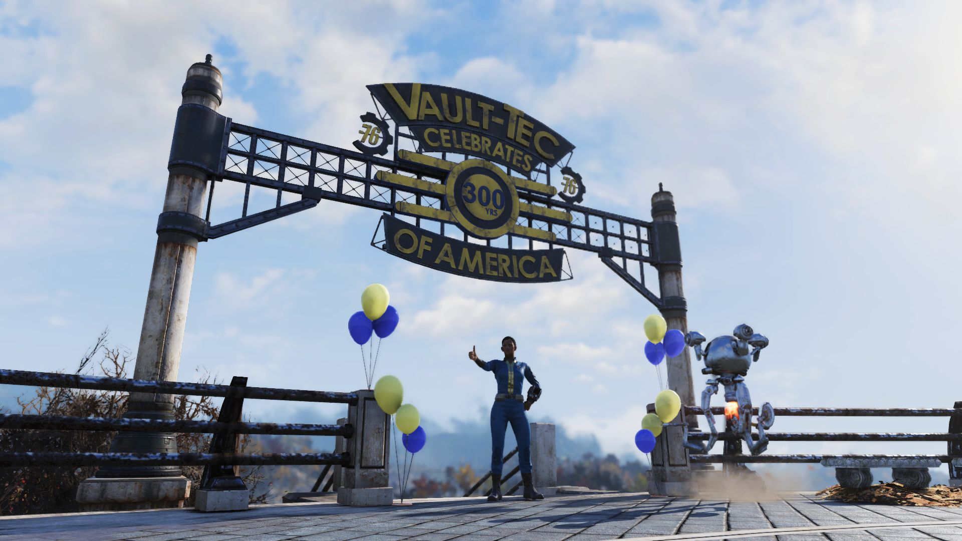 A player in a blue and yellow Vault-Tec jumpsuit stands giving the thumbs up under a large sign reading 'Valt-Tec Celebrates 300 Years of America. There are some yellow and blue balloons either side of them.