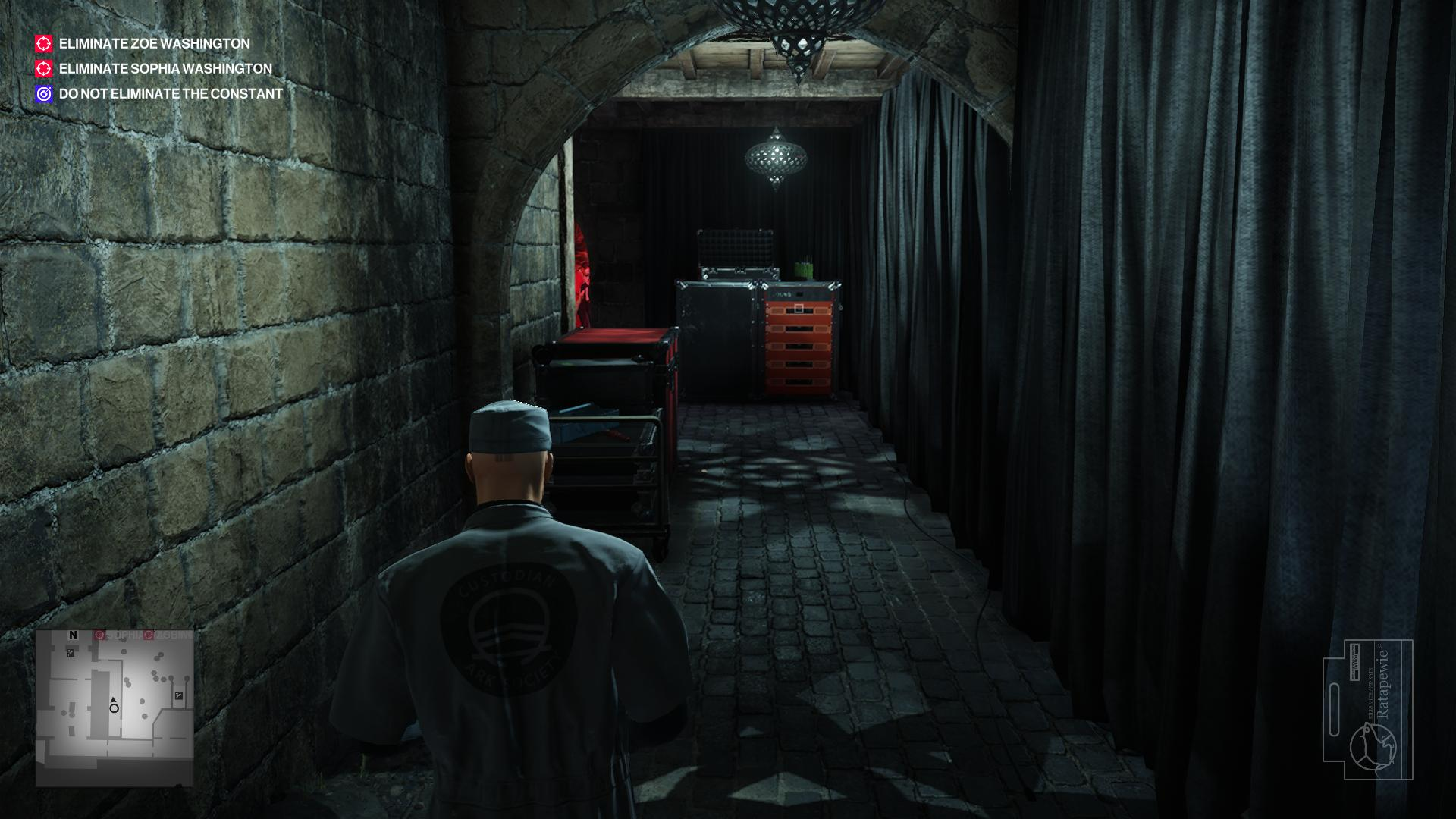 Agent 47 in a maintenance worker's outfit, walking through a corridor. Curtains are to the right and a disco ball is overhead.