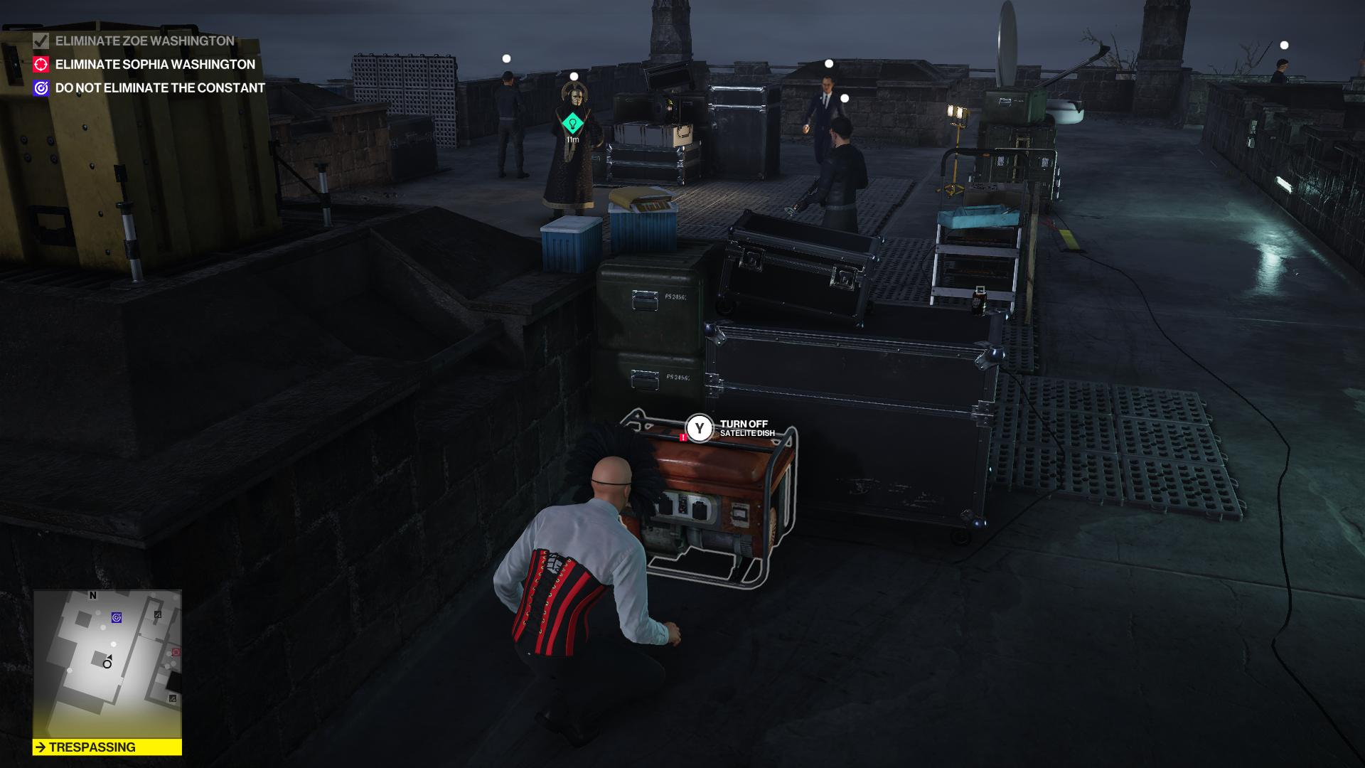 Agent 47 hiding from armed guard, the Constant, and a cultist. The controls to a satellite are next to him.