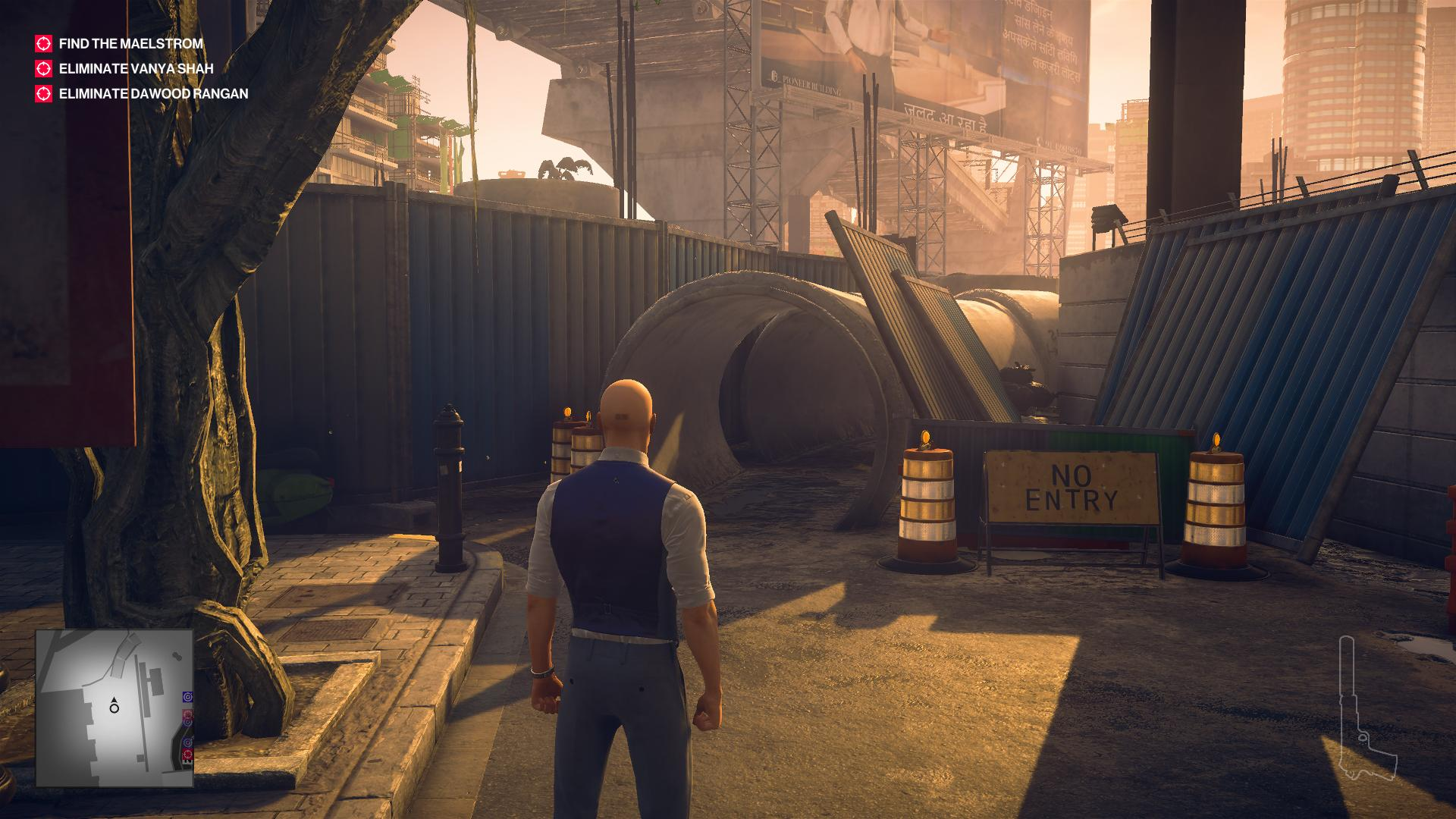"Agent 47 in casual wear about to enter a cement pipe. There is a sign that says ""No Entry"" just before it."