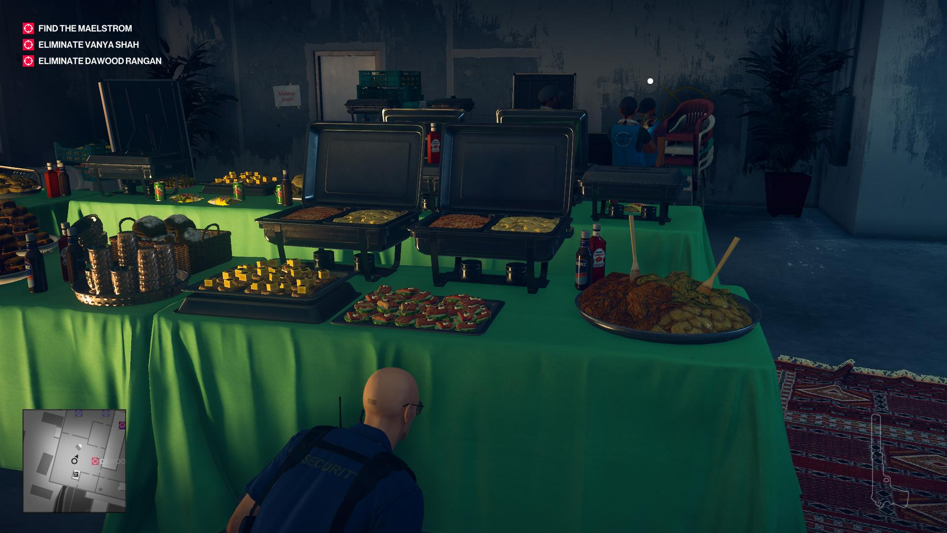 Agent 47 sneaking around as a security guard, behind a buffet table filled with Indian cuisine.
