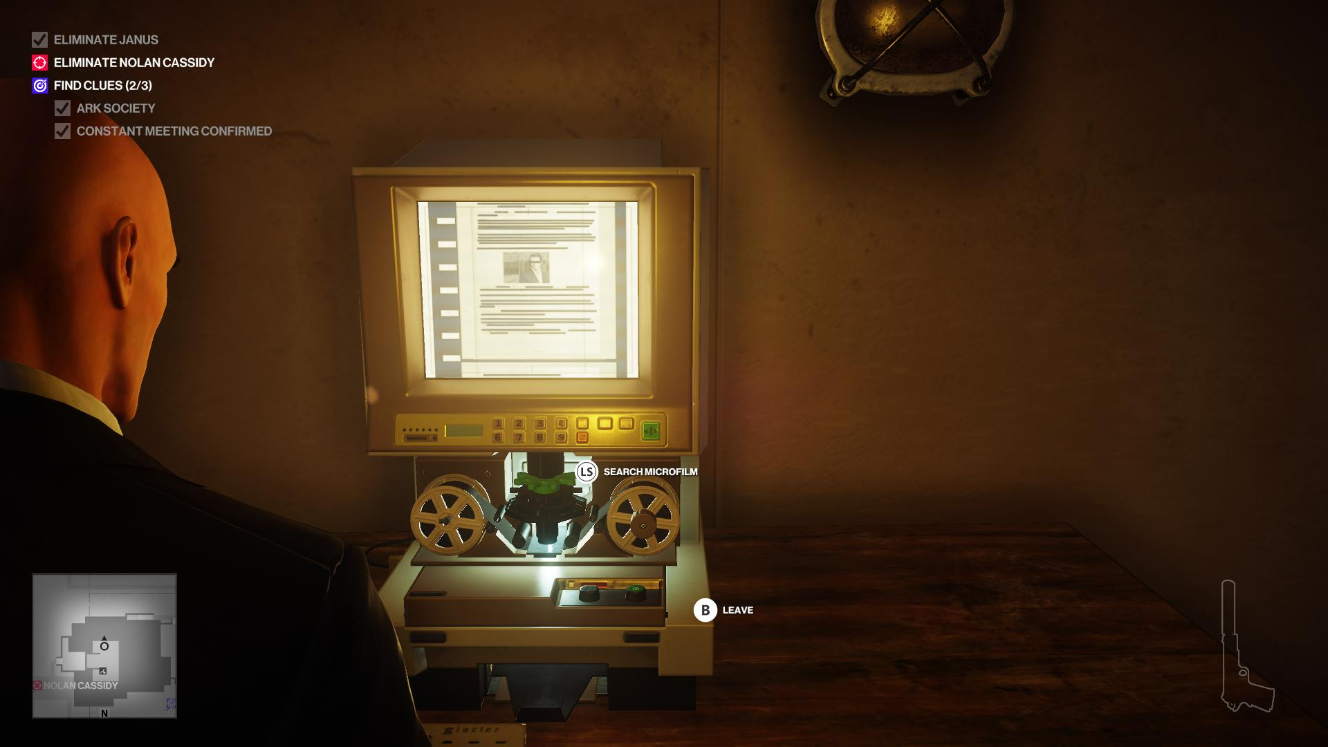 Agent 47 examining microfilm on a microfilm reader.