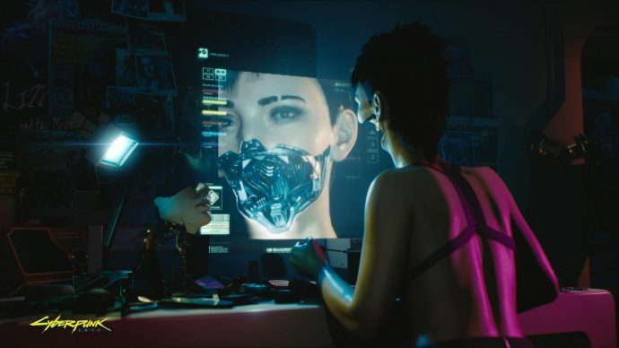 A woman staring at a monitor with half her cybernetic face off.