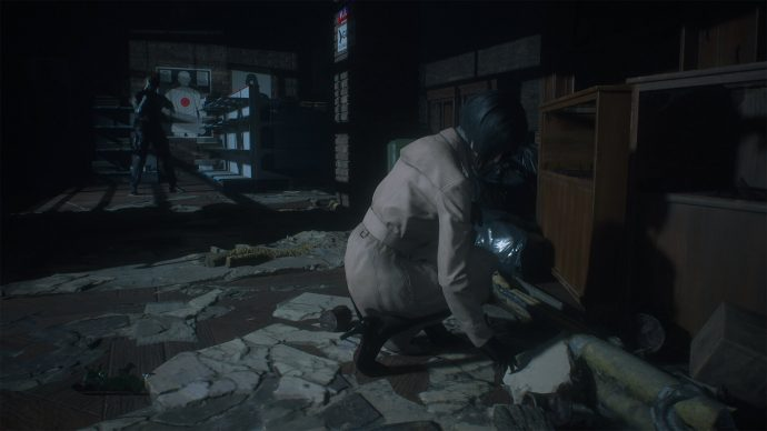 Ada Wong searching for clues in an abandoned shop while Leon Kennedy keeps a lookout for zombies.