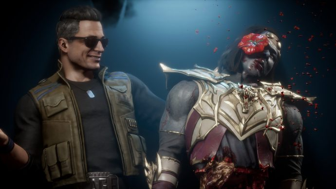 Johnny Cage holding Liu Kang like a ventriloquist dummy, as a tomato hits Liu Kang in the face.