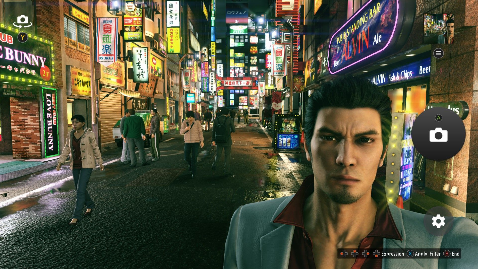 Kazuma Kiryu, Yakuza protagonist, is taking a selfie of himself in Kamurocho. The street behind him is narrow and crowded with bright store signs.