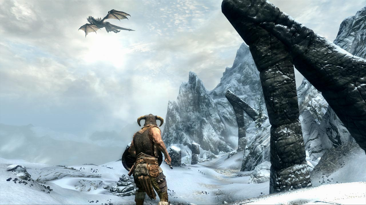 A screenshot from The Elder Scrolls V: Skyrim showing the dragon born, back to camera, standing on a snowy mountain. Up in the sky, a dragon is flapping about.