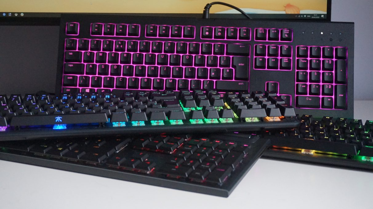 A collection of gaming keyboards on a table.