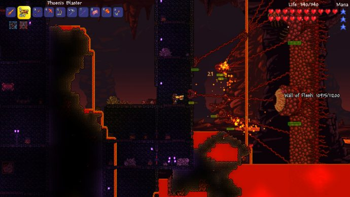 The player is cornered between the Wall of Flesh boss and a cliff in Terraria's hell biome.