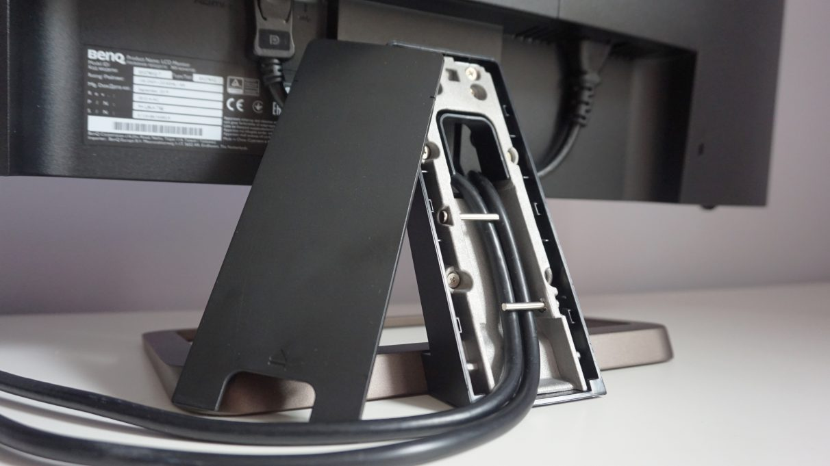 A close-up image of the BenQ EX2780Q's stand with its power and display cables threaded beneath it