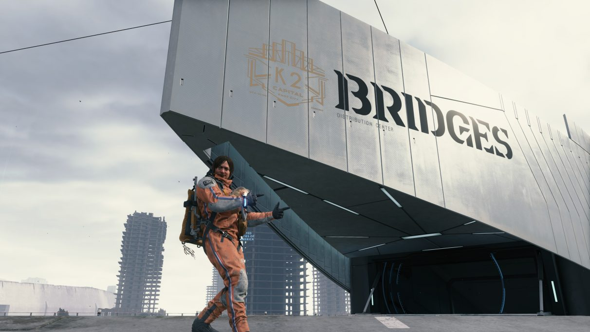 A screenshot of Sam Bridges doing a thumbs up sign outside a Bridges depot facility in Death Stranding.