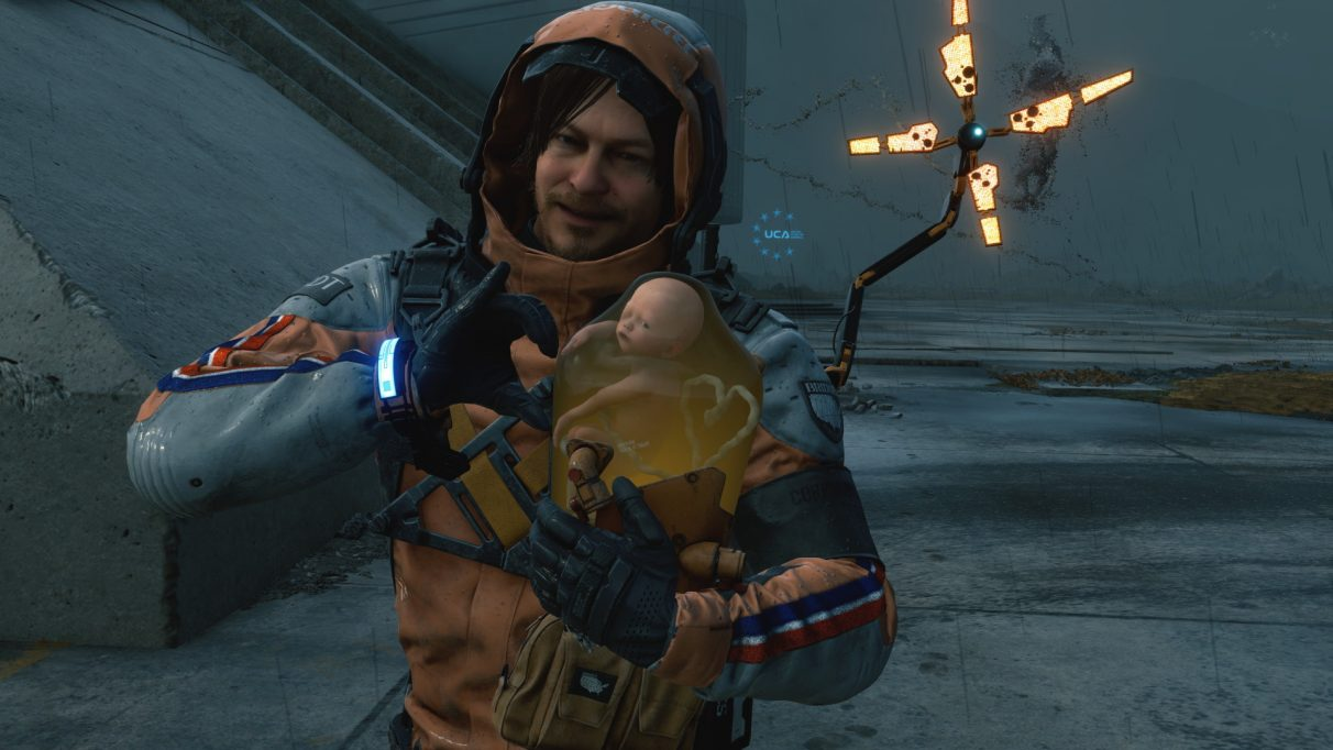 A screenshot of Death Stranding showing Sam Bridge making a heart shape with BB using the game's photo mode.
