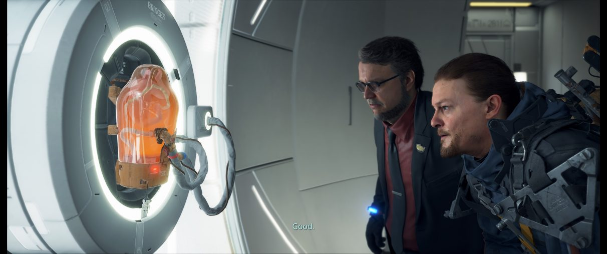 A screenshot of Death Stranding's Sam Bridges and Deadman inspecting a sleeping BB in an ultrawide aspect ratio.