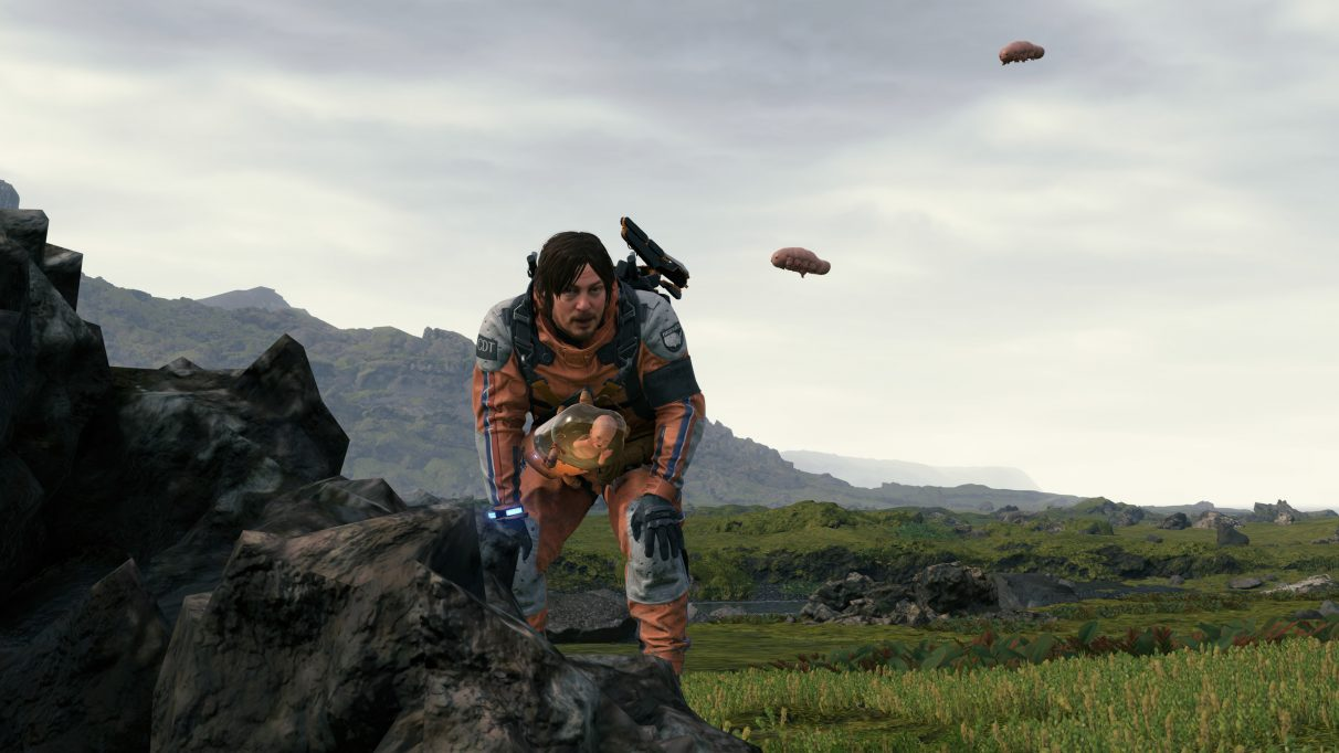 A screenshot from Death Stranding showing Sam Bridges bending over to look at some floating cryptobiote life forms.