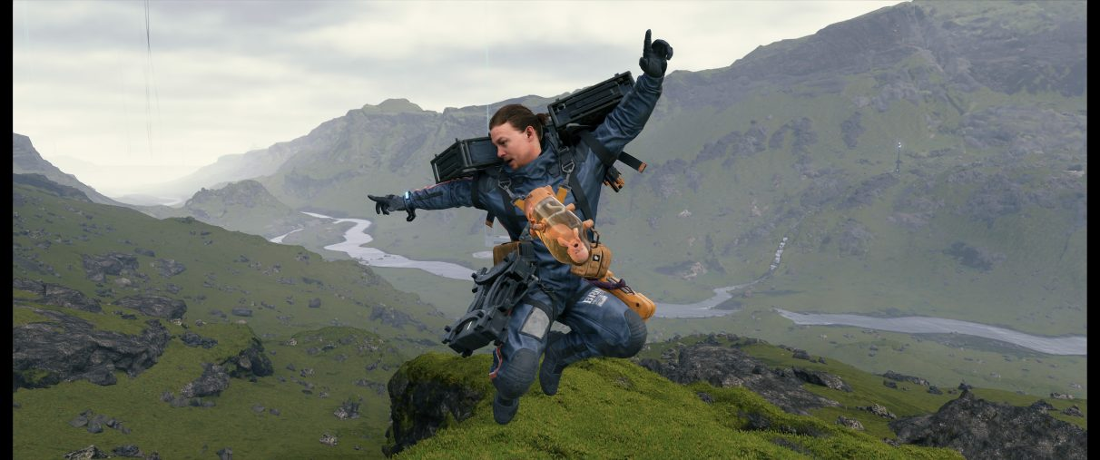 A screenshot of Sam Bridges jumping in mid-air on a mountain top as he looks down onto the valley below.