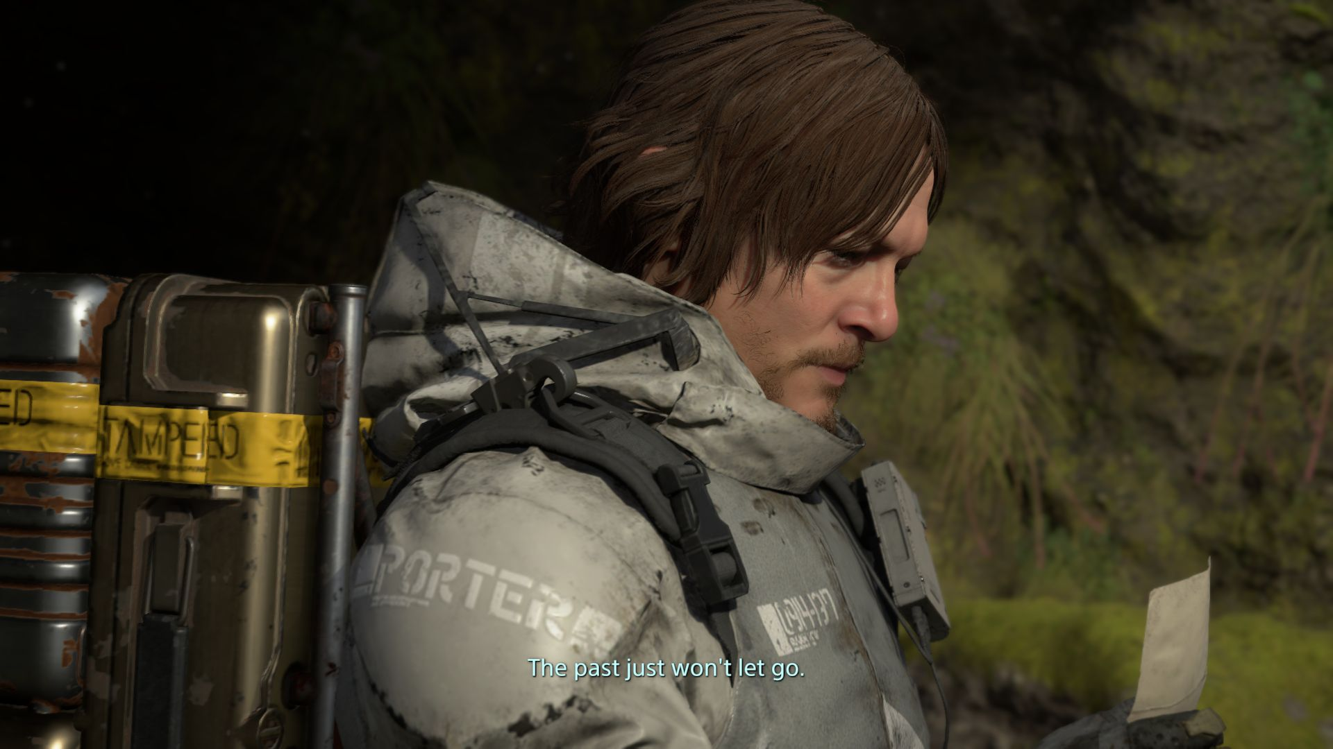 A screenshot of Death Stranding showing the protagonist looking at a sad photo