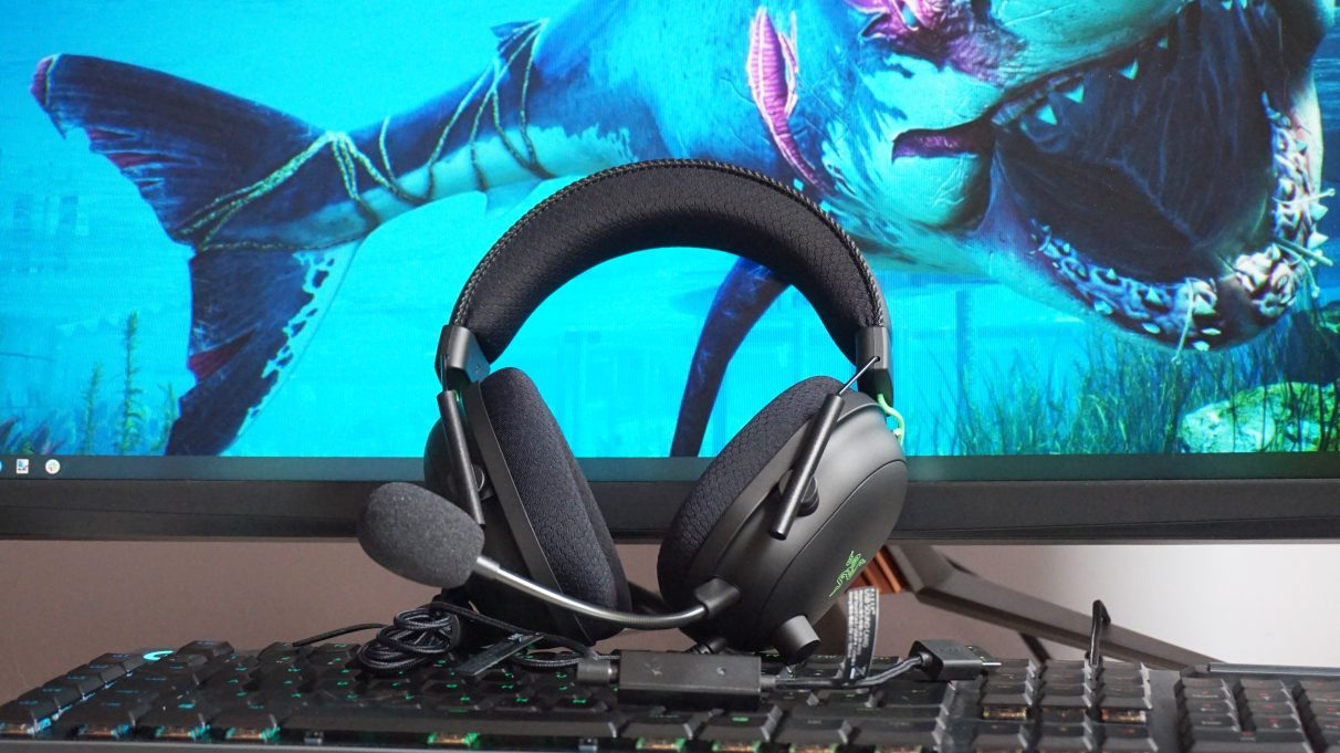 A photo of the Razer Blackshark V2 gaming headset perched on top of a keyboard and resting against a monitor with a shark wallpaper.