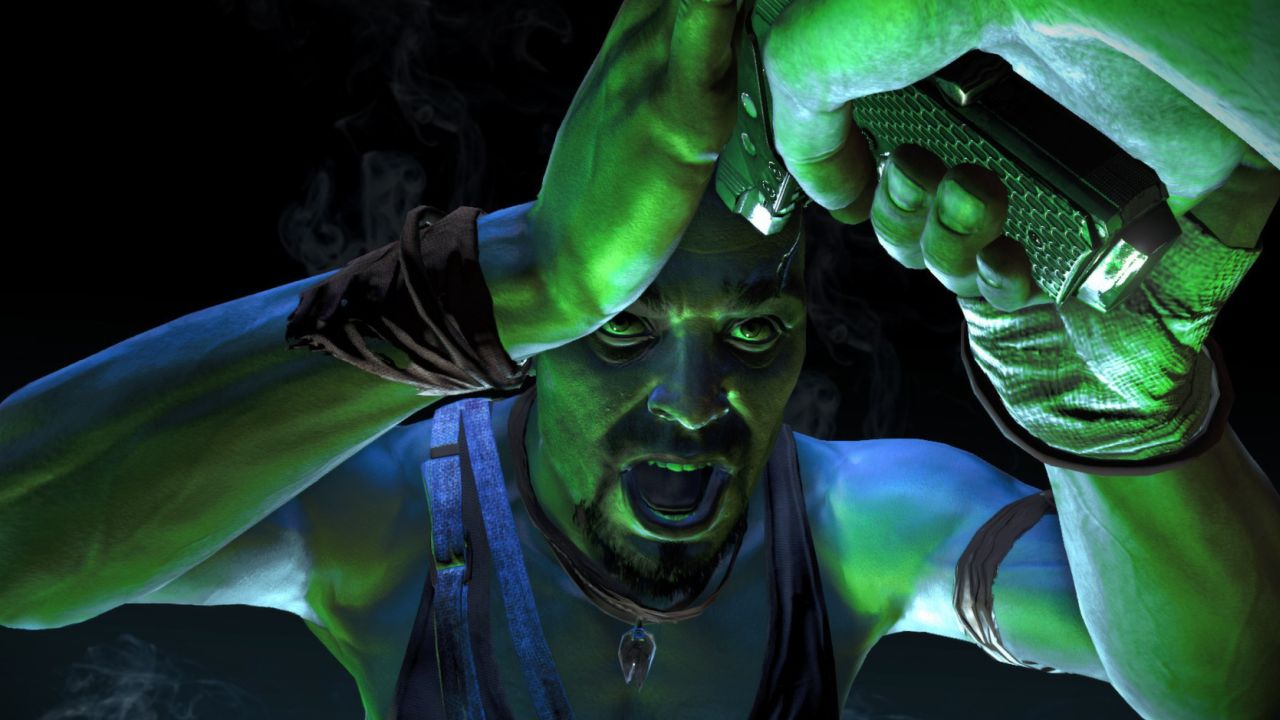 An image from Far Cry 3 of much lauded antagonist Vaas, a man in his 30s with a short mohawk and a dark goatee. The lighting is sickly green. Vaas is forcing the protagonist to hold a pistol up to his forehead. He looks angry and very intense.
