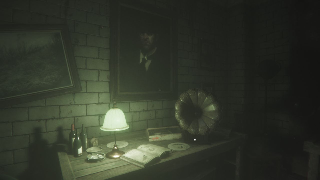 A screenshot of a safe room in Maid Of Sker, showing a desk with a green lampshade on the left, a gramophone on the right, and a book in between them. On the wall behind is a portrait of a glowering man.