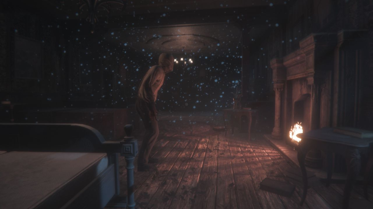 A screenshot of a room in Maid Of Sker. The only light comes from a fireplace on the left hand side. It throws light on thick dust motes in the air. In front of the fireplace stands an enemy, with a sack mask on his head. He is paused, listening.