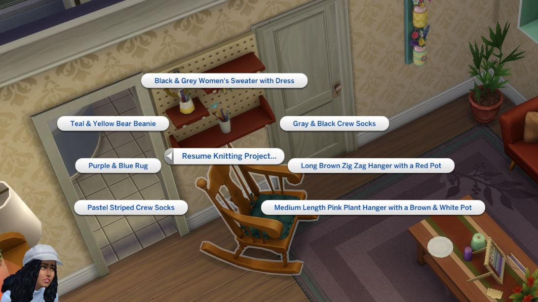 A screenshot showing a rocking chair in The Sims 4 Nifty Knitting. The action radial menu is open to 'Resume Knitting Project' over it. There are many projects to resume, including 'Black & Grey Women's Sweater With Dress', 'Teal & Yellow Bear Beanie' and 'Medium Length Pink Plant Hanger with A Brown & White Pot'. In the bottom left corner, the Sim's character portrait is looking sad and stressed.