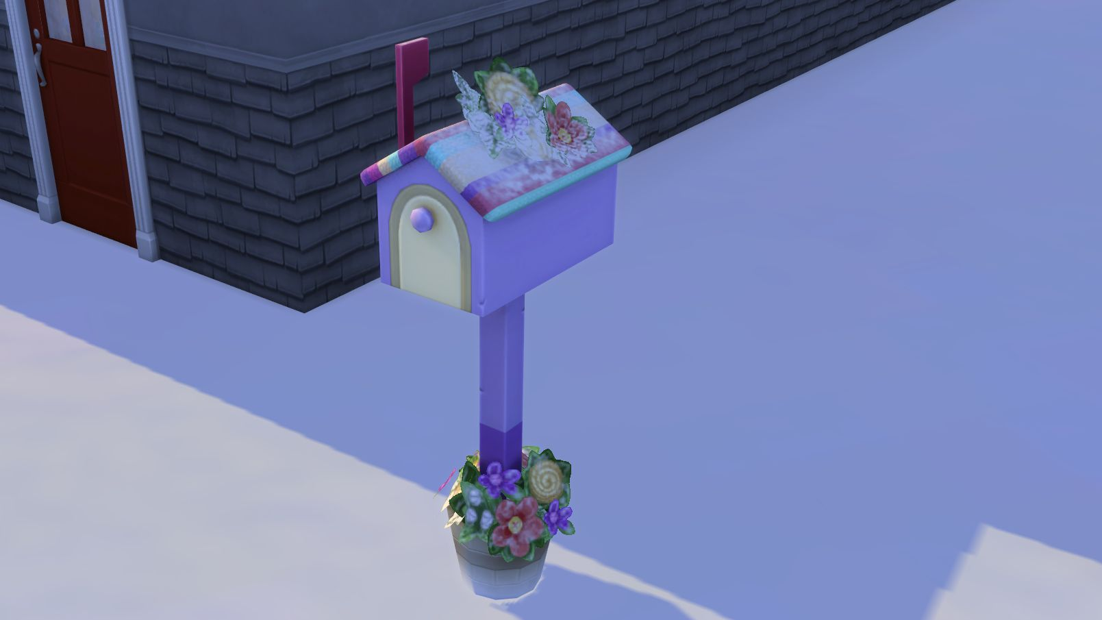 A knitted mail box cover from The Sims 4 Nifty Knitting. It is purple, with a knitted striped roof in pink, purple, turquoise and yellow, and has fake flowers made from yarn also. No real person would have this outside their home. Also, it has been dusted with fresh snow.
