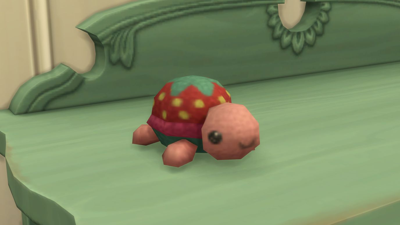 A screenshot from The Sims 4 Nifty Knitting showing a tiny tortoise plushie made of wool. It has pink skin and a red shell with seeds and leaves on top like a little strawberry. And it is smiling because it is very cute.