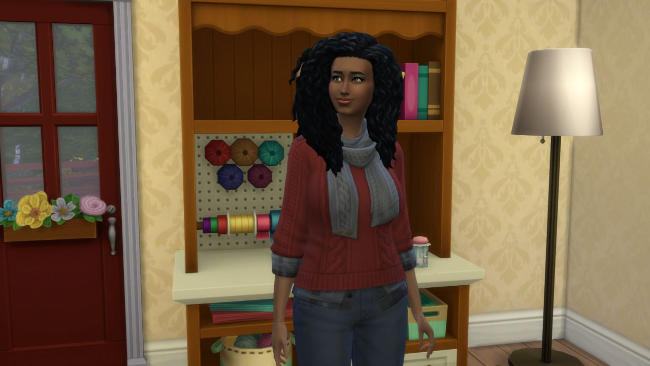 The Sim stands proudly in front of a craft shelf that has rolls of ribbon, some wool, and some project baskets in its shelves and cubbies. She is wearing a red knitted jumper with an inbuilt charcoal grey scarf. She looks proud of her weird knitting life.