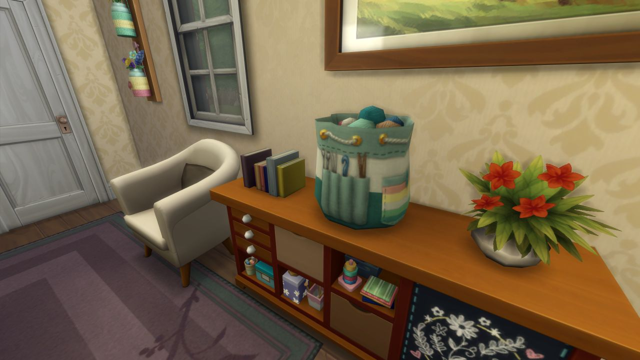 A screenshot of some new furniture from The Sims 4 Nifty Knitting, showing a new sideboard from the stuff pack that has lots of little cubbies for craft things. On top of it is a pot of flowers and a drawstring bag full of balls of wool, with crochet hooks and knitting needles in pockets on the side.