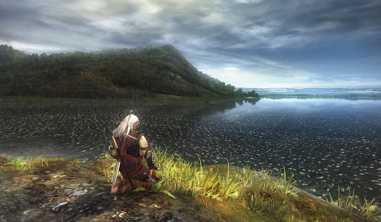 Geralt from The Witcher knees on a grassy bank overlooking a huge lake, with a mountain in the distance. It's pretty, for 2007.