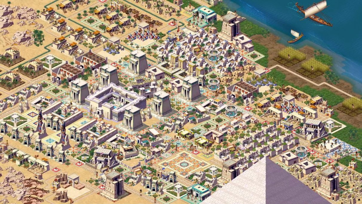 A second promotional screenshot of a city in Pharaoh: A New Era. This city is more grand. The banks of the Nile are visible on the top right corner, and the tip of a pyramid pokes up from the bottom of the screenshot.
