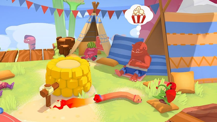 A screenshot from Phogs, where a bipedal monster man with red skin is sitting by a tent in the background. A speech bubble shows that he wishes for some popcorn. In the foreground the Phog, a dog with one head at either end of its body, is trying to heat a brick oven, by means of one head eating from a chilli plant, thus causing the other head shooting flames from its mouth.