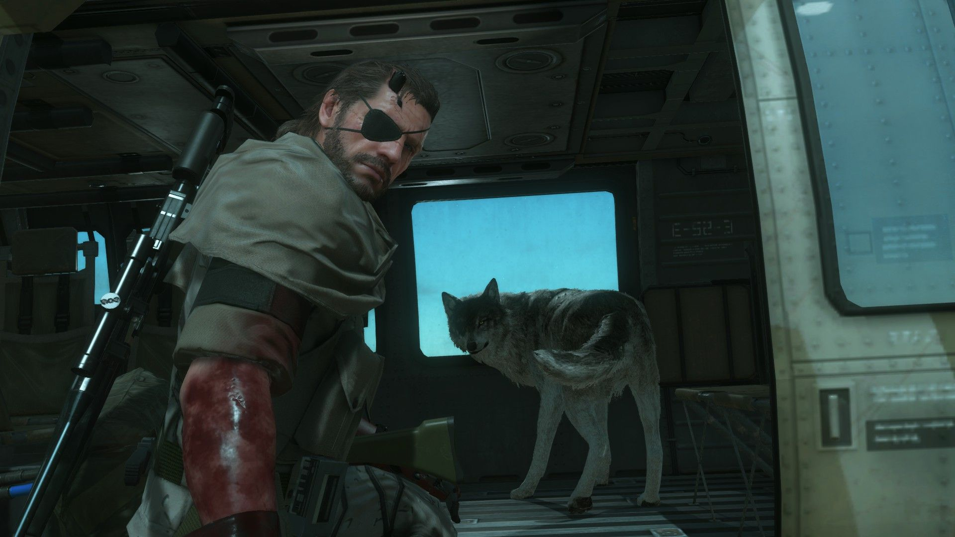 A screenshot of the interior of a helicopter from Metal Gear Solid V showing snake, with his cool eyepatch, kneeling inside. Behind him, his cool wolf dog Diamond Dog has turned to snarl at the camera.