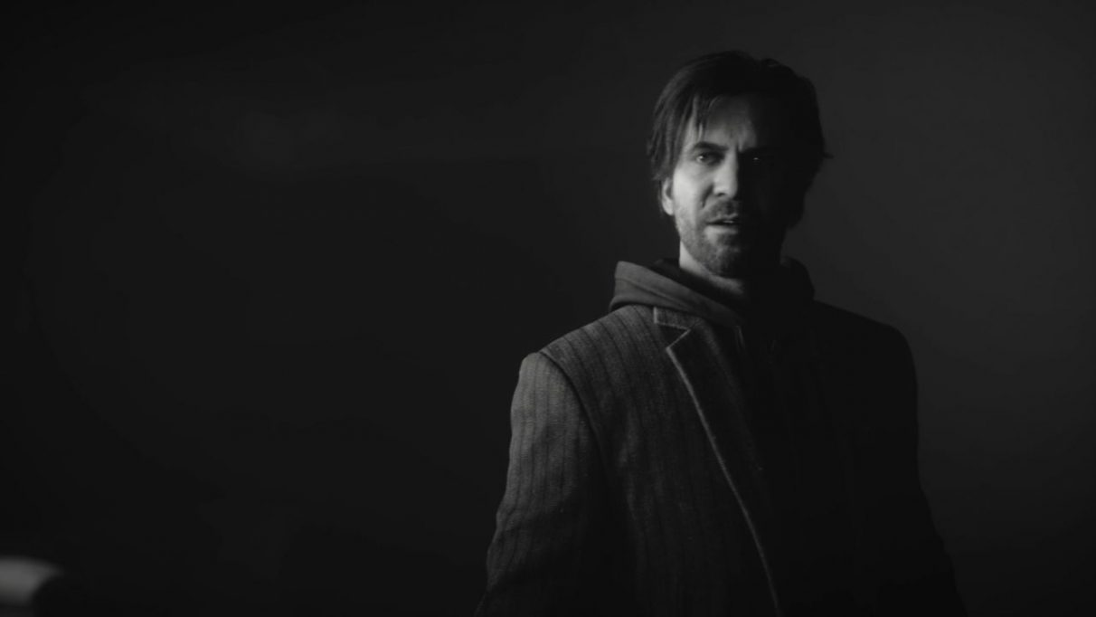 A screenshot from Control's AWE DLC showing Alan Wake, a tired looking bearded man in his mid to late 30s. He is wearing a suit jacket over a blazer, like a fool.