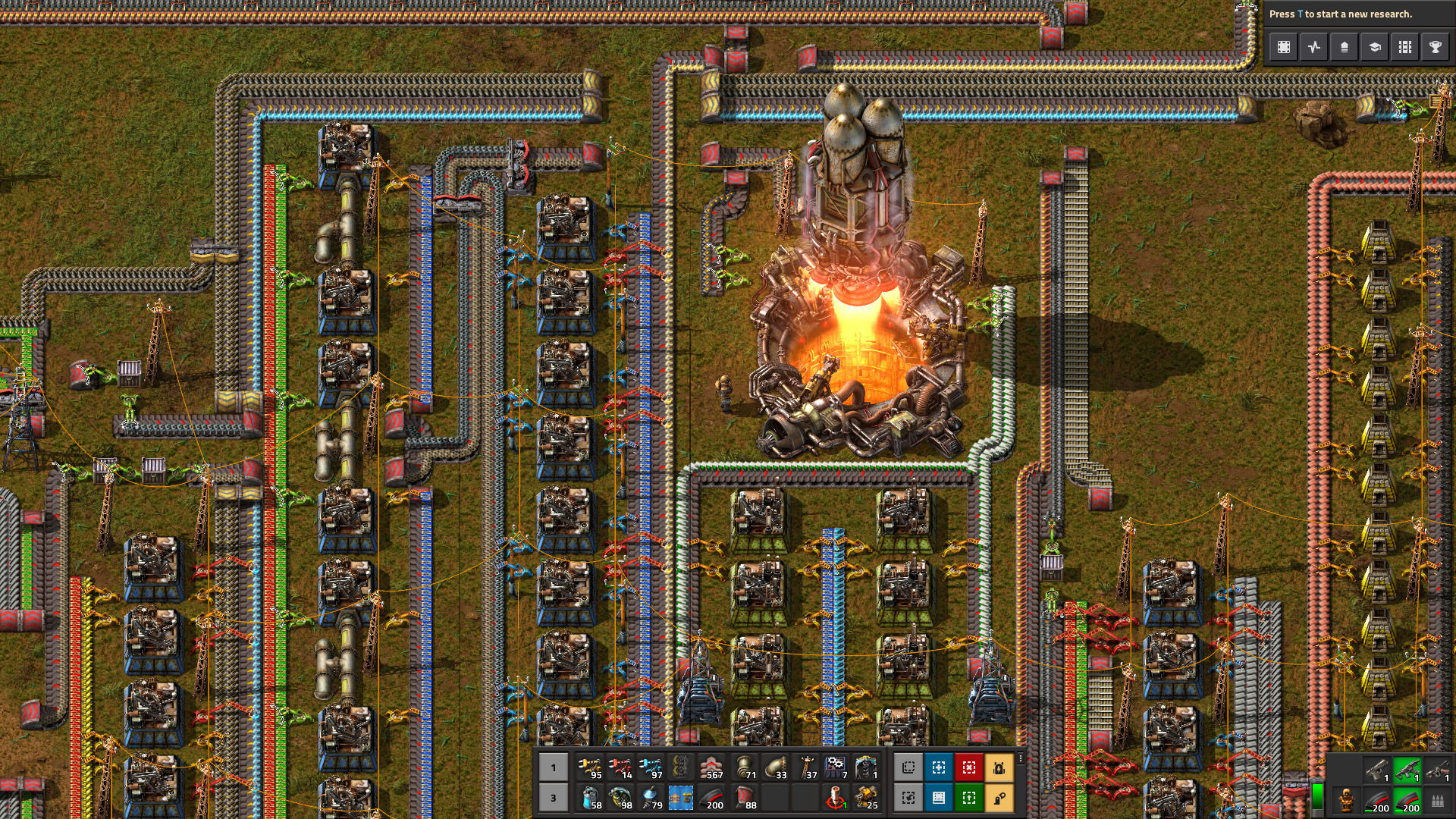 A screenshot showing, from an aerial view, a complex production line of little machines and engines in Factorio. They are arranged around the glowing eye of a huge furnace.