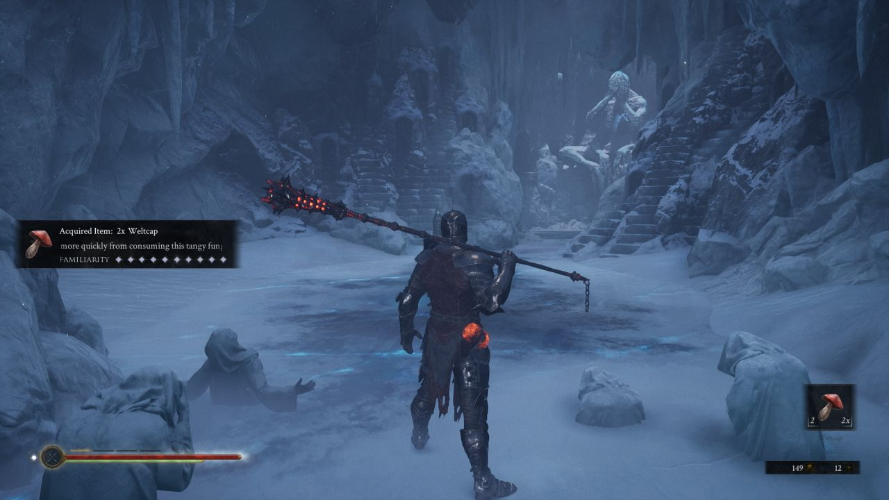 A screenshot from Mortal Shell showing the player character, still in plate armour but wielding a large mace over one shoulder, looking into a cave. The floor is ice, and statues of hooded figures in anguish are half encased in it next to the player. At the other end of the room is a large humanoid statue in a seated position.