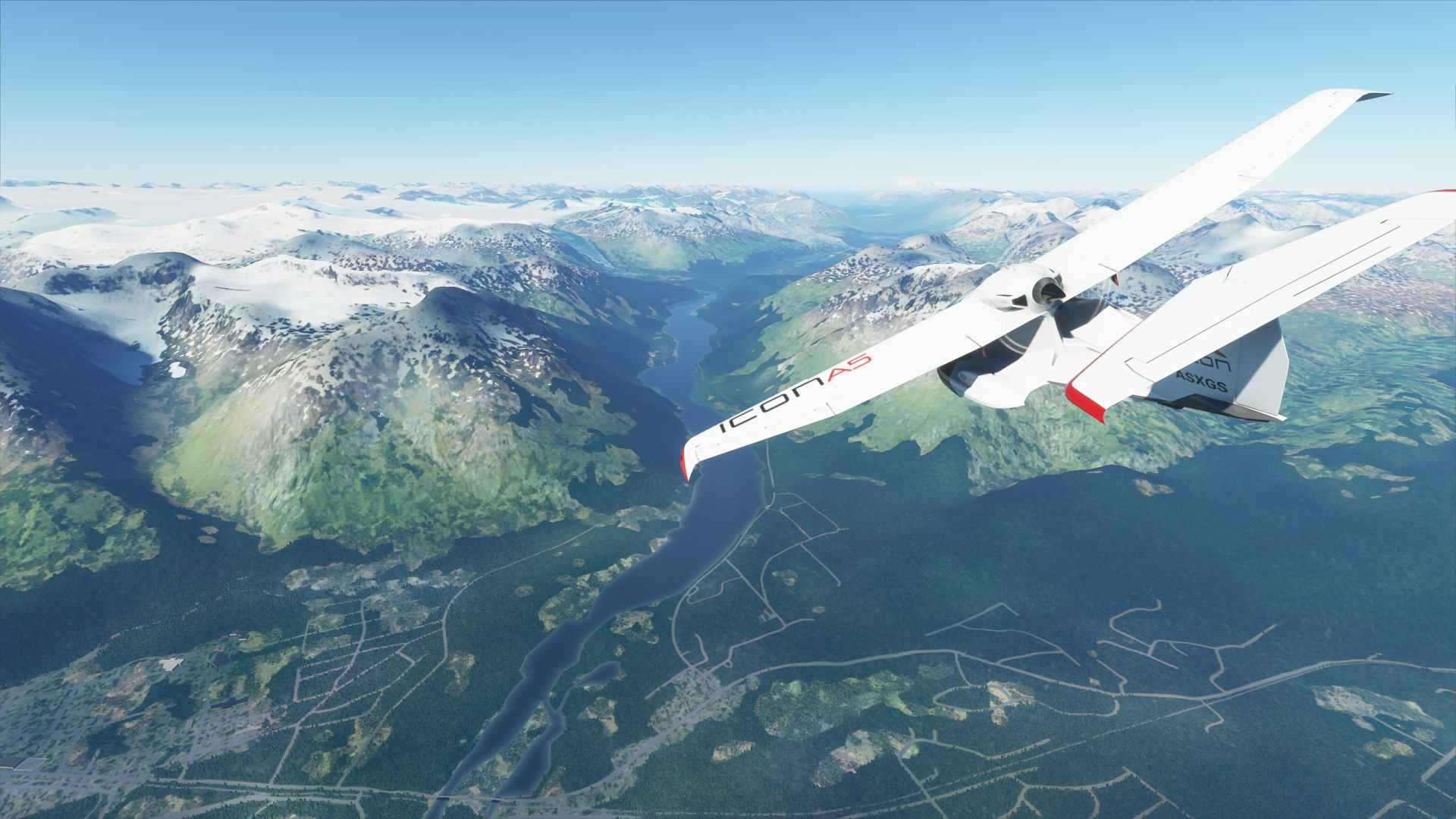 A Microsoft Flight Simulator screenshot. A small plane flies over the Alaskan landscape. A flat river runs between two mountains.