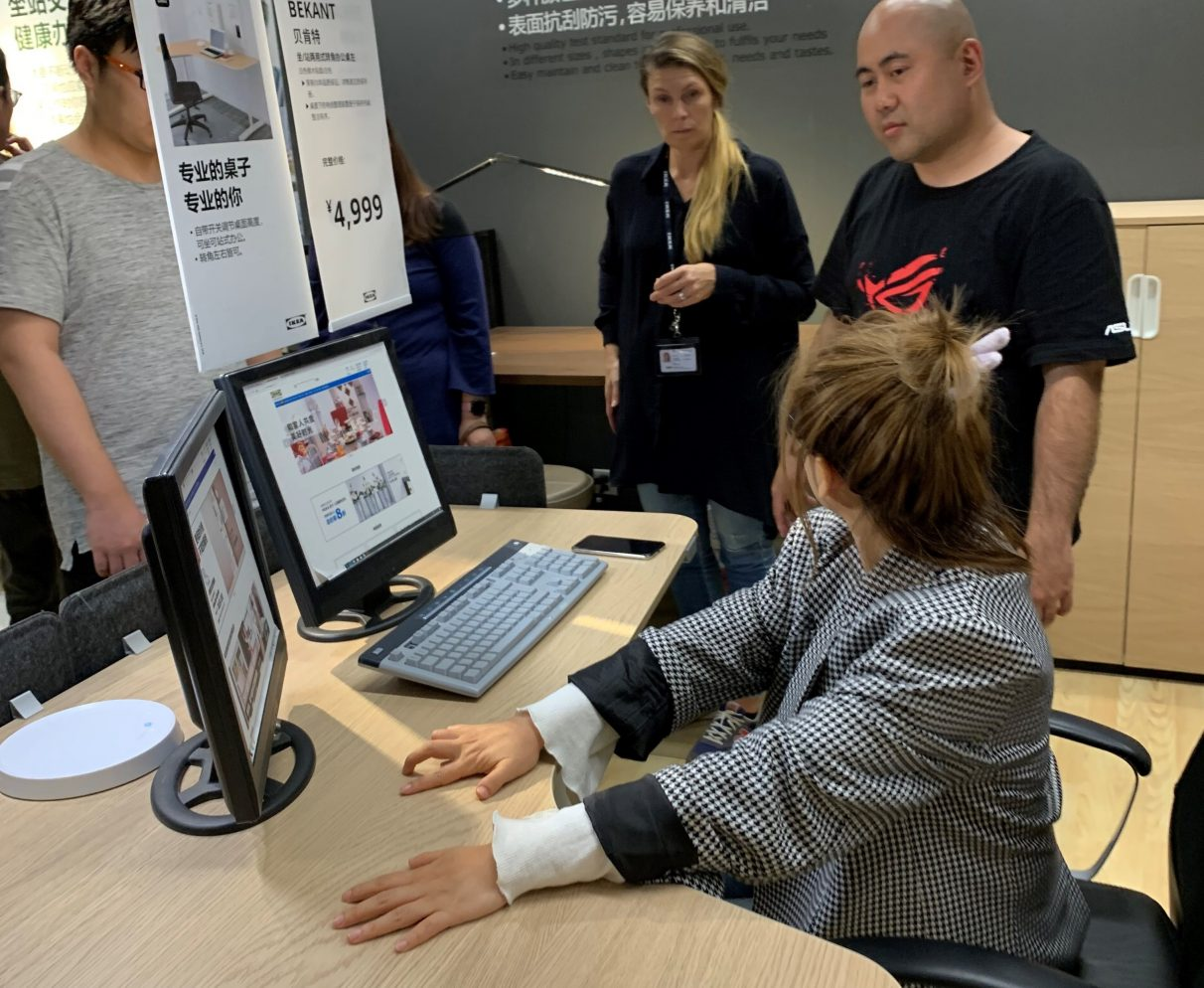 An photo from one of Asus and Ikea's design workshops, showing an Asus representative standing beside a woman seated at an existing Ikea desk.