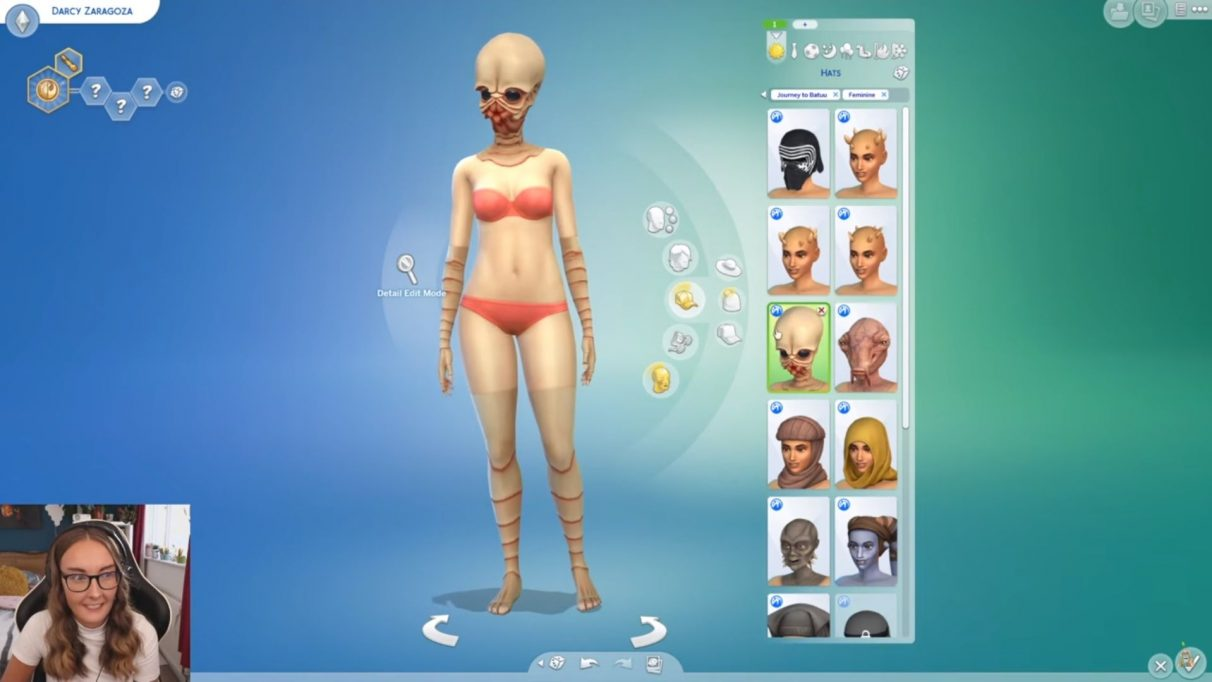 A screenshot from EnglishSimmers video on the Journey To Batuu Create A Sim options. It shows her Sim as a Bith alien, which means they have a normal torso and then are wearing a Bith mask and have, essentially, gloves and tights on to make their arms and legs look Bith-y as well. It is very funny.
