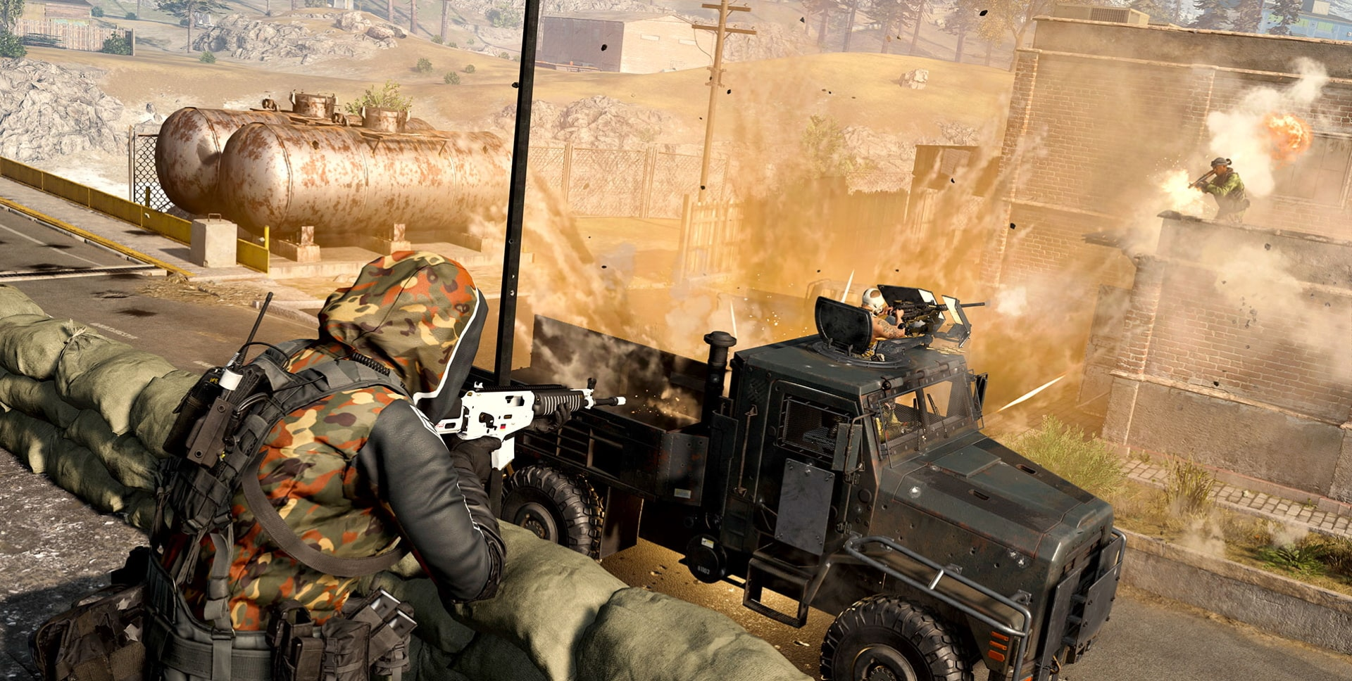 A screenshot from Warzone Season 6 which shows two players flanking an armoured truck. One fires an RPG, while the other aims an assault rifle at it.