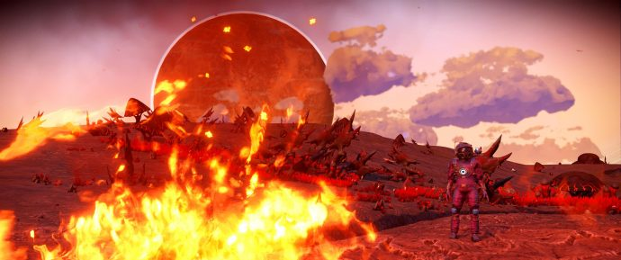 A screenshot of a big fire and a planet cresting the horizon while the player looks on in No Man's Sky.