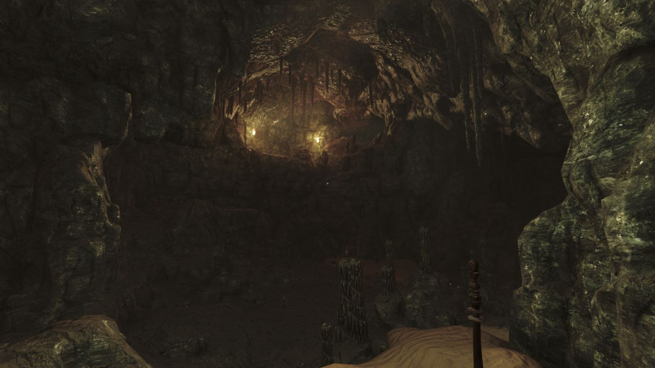 A screenshot of a dark and gloomy cave in Amnesia: Rebirth. It is full of stalactites and stalagmites, but the presences of two lit torches on a higher ledge are evidence that someone else has been here.