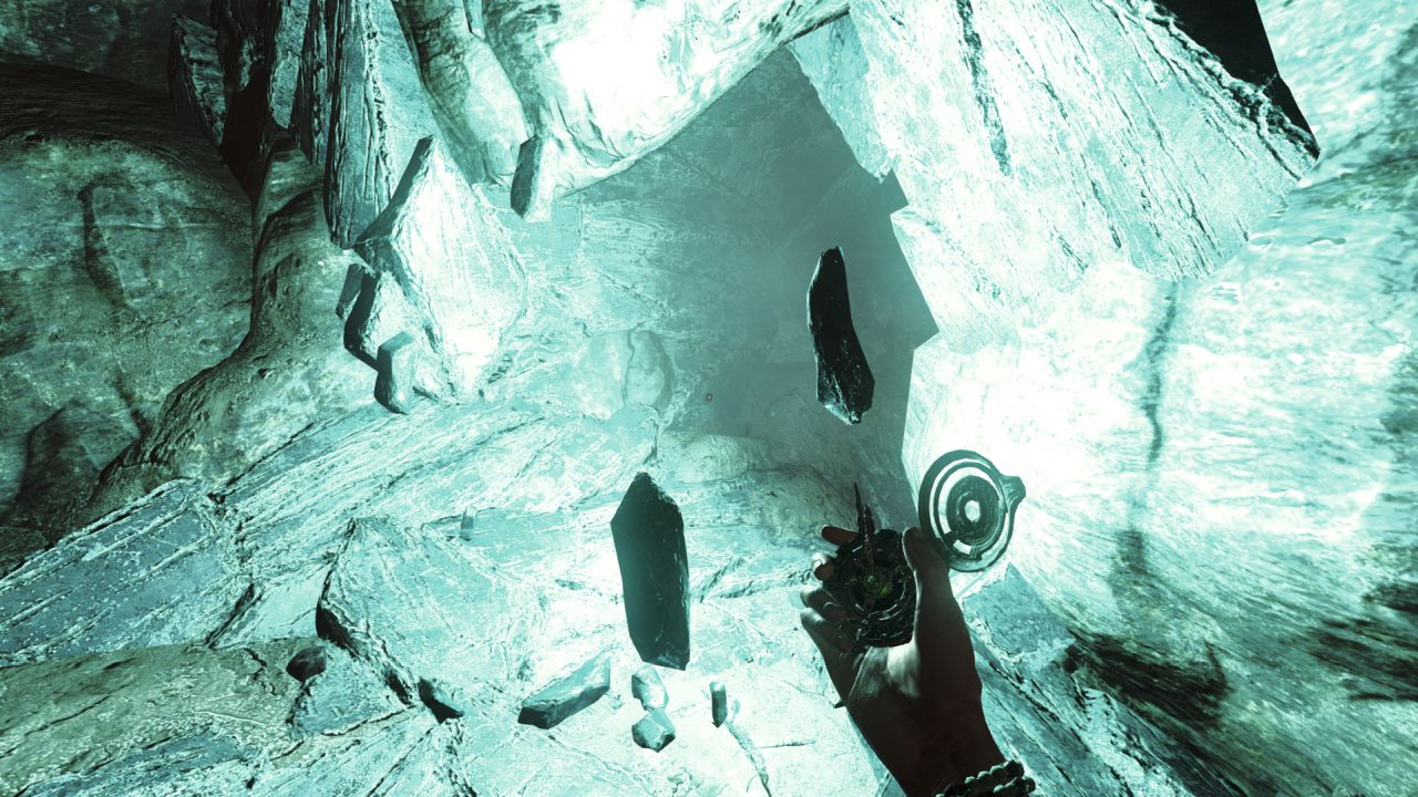 A screenshot of the Player character's hand in Amnesia: Rebirth, holding a kind of compass. The rock wall in front of them has opened up a gap that is emitting bright blue light. Several shards of rock are levitating around it.