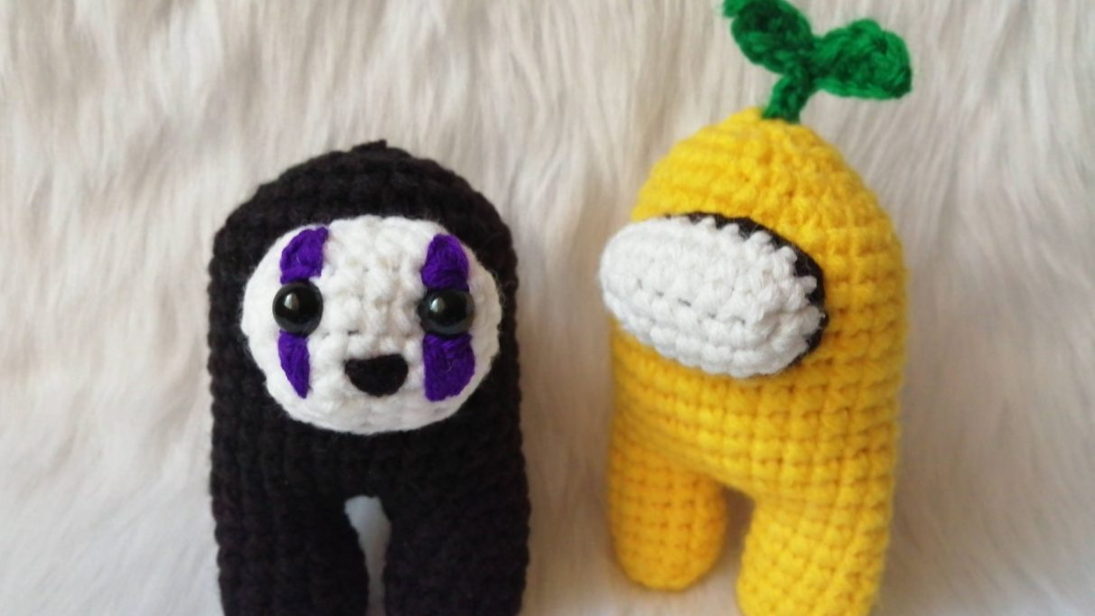 A picture of two teeny crewmate amigurumi - stuffed crocheted figures - of Among Us crewmates made by Reddit user prudence0381. One is a yellow crewmate with a little seedling sprouting out of the top of its head. The other is black, and resembles No Face from Spirited away, although it looks very happy.