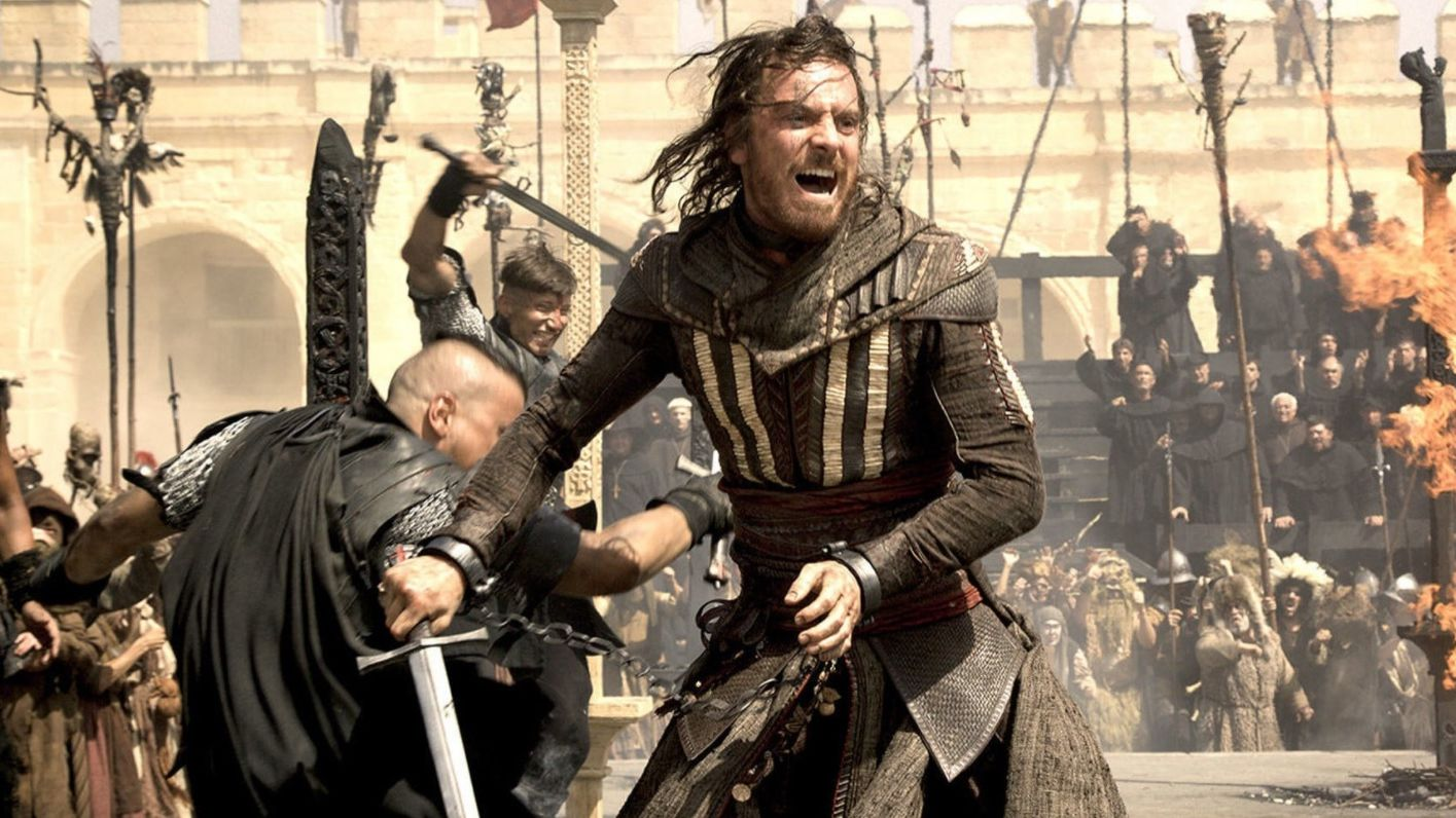 A still from the Assassin's Creed movie. Michael Fassbender, as the assassin Aguilar, is escaping from a sticky situation. His hands are chained together but he's wielding a sword and things in the background are on fire.